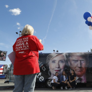 People pose for a photo kneeling near a bus adorned with photos of candidates Hillary Clinton and Donald Trump before the presidential debate at Hofstra University in Hempstead, N.Y., Monday, Sept. 26, 2016. (AP Photo/Mary Altaffer)