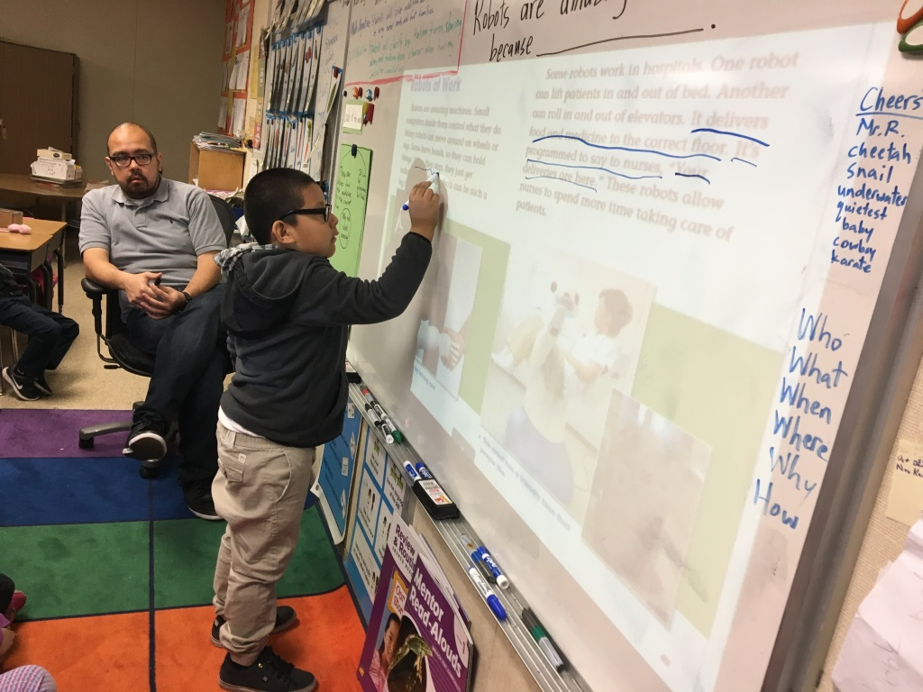 Michael Ramirez, a first-grade teacher at 20th Street Elementary School just south of downtown L.A., teaches a lesson in his bungalow classroom on Dec. 6, 2017. (Photo by Kyle Stokes/KPCC)