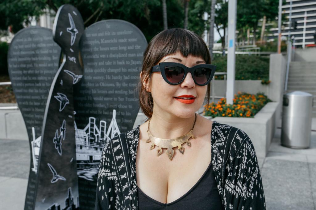 Artist Miyo Stevens-Gandara stands next to her angel,