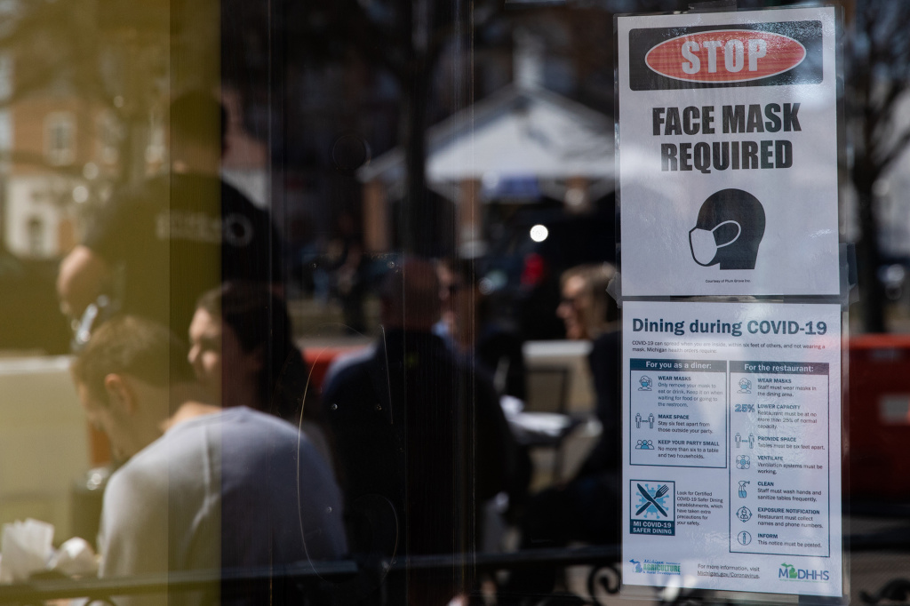 A sign requiring face masks and COVID-19 protocols is displayed at a restaurant in Plymouth, Mich., on March 21. Coronavirus cases in Michigan are skyrocketing after months of steep declines, one sign that a new surge may be starting.