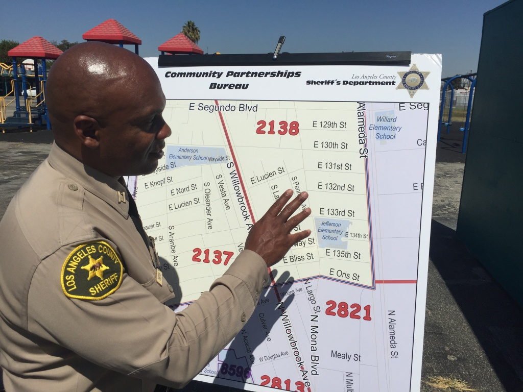 LA County Sheriff's Captain Kerry Carter, who heads the Century Station, points out where deputies will be walking door to door to build community trust in Willowbrook near Compton.