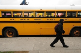 A student on his way to school walks past a Los Angeles Unified School District (LAUSD) school bus.