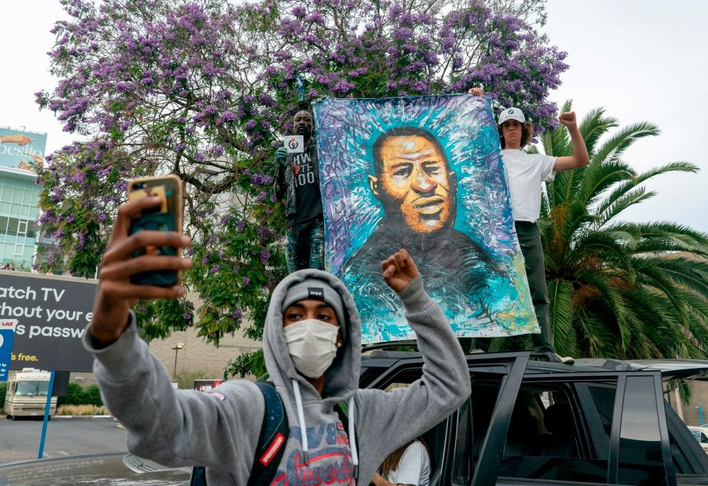 A protester poses next to a painting for George Floyd's family in Hollywood after curfew during a demonstration over the death of George Floyd while in Minneapolis Police custody, in Los Angeles, California, June 2, 2020. - Anti-racism protests have put several US cities under curfew to suppress rioting, following the death of George Floyd in police custody. (Photo by Kyle Grillot / AFP) (Photo by KYLE GRILLOT/AFP via Getty Images)