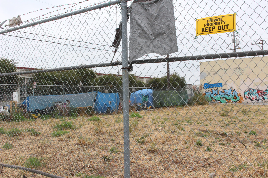 """The belongings of people living on a sidewalk in East Oakland sprawl next to an empty lot on Aug. 24, 2018. Homeless advocate Candice Elder, 34, said vacant properties dot the area. """"A lot of properties were vacant when I was growing up, and they are still vacant now,"""" said Elder, a native of the city."""