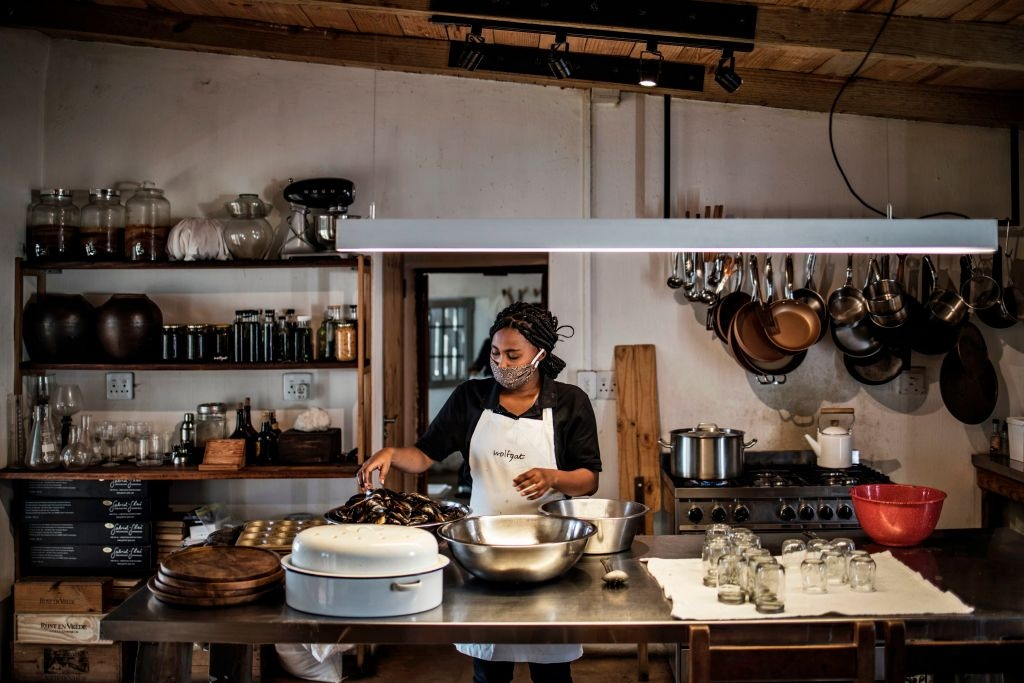 Emily, a cook with the South African Chef Kobus van der Merwe of the Wolfgat restaurant on the beach in Paternoster, works on a steamy load of freshly cooked mussels in the restaurants kitchen on June 18, 2020.