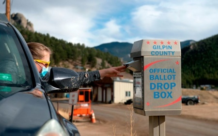 A voter drops off her ballot for the U.S. presidential election on Nov. 3, 2020, in Rollinsville, Colo. Colorado's voting laws got fresh attention this week after the MLB decided to move its All-Star game to the state to protest Georgia's new legislation.