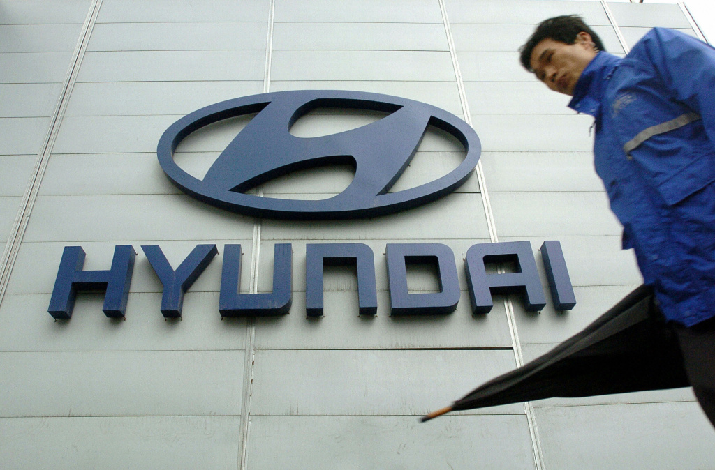 A man walks past a logo of Hyundai motor displayed in front of its headquarters in Seoul, South Korea.