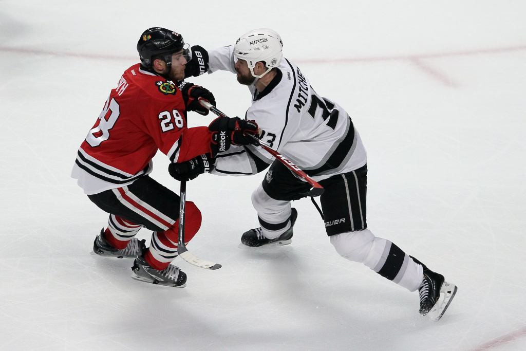 Ben Smith #28 of the Chicago Blackhawks checks Willie Mitchell #33 of the Los Angeles Kings during Game Seven of the Western Conference Final in the 2014 Stanley Cup Playoffs at United Center on June 1, 2014 in Chicago, Illinois.