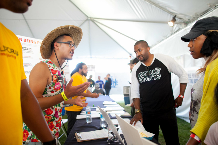 Matthew Vu, left, talks to local residents about issues that will be on the ballot during a music and art festival in Martin Luther King Jr. Park in South Los Angeles on Saturday, Sept. 3, 2016.