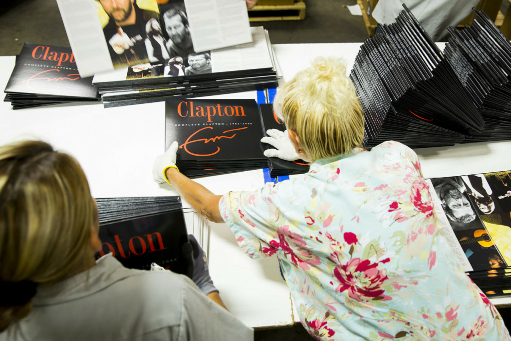 Workers prepare Eric Clapton vinyl album jackets for shipping at Stoughton Printing in 2014. Stoughton offers health insurance through a plan in which small businesses jointly purchase coverage.