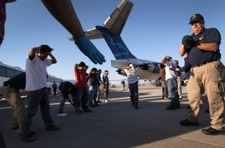 Guatemalan nationals are searched before boarding a deportation flight to Guatemala City, Guatemala at Phoenix-Mesa Gateway Airport, June 24, 2011. Some immigrant advocates, joined by Latino and labor groups, are calling on the White House to suspend deportation of immigrants who might qualify to legalize their status under a Senate immigration reform bill.