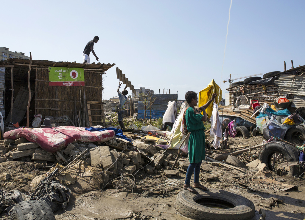 Workers repair the roof of a small shop while a woman hangs clothing to dry among debris in Beira, Mozambique. The city was badly damaged after Cyclone Idai hit on March 14.