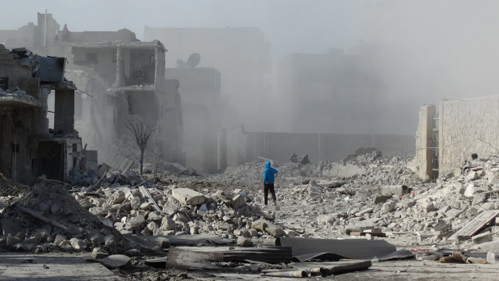 A Syrian man walks through debris following an alleged air strike by Syrian government forces on Friday in the northern city of Aleppo. Nearly 1,900 people have been killed in Syria since peace talks opened in Switzerland on Jan. 22, the Syrian Observatory for Human Rights said.