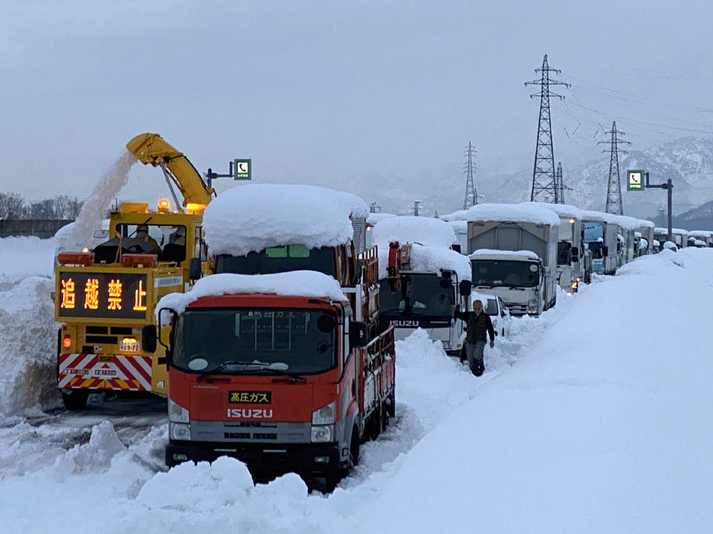 A snowplow clears a path beside cars stranded on the snow-covered Kan-etsu Expressway at the city of Minamiuonuma in Japan's Niigata Prefecture on Friday.