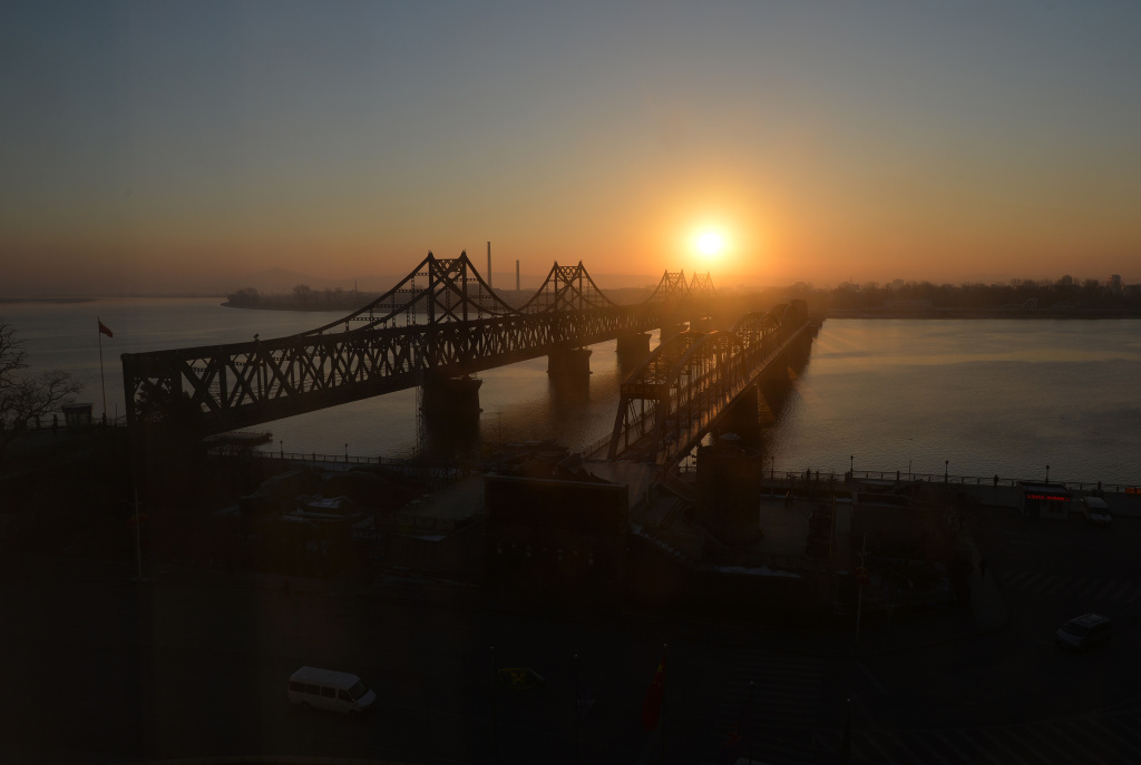 The sun rises over the Sino-Korean Friendship Bridge which spans the Yalu River and leads into North Korea (background) at the Chinese border town of Dandong.