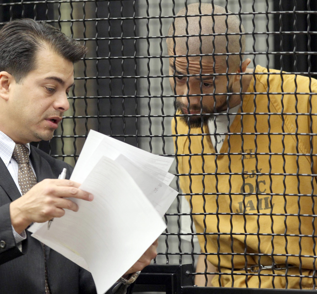 In this file photo, defendant Itzcoatl Ocampo confers with attorney Randall Longwith during Ocampo's arraignment Tuesday Feb. 21, 2012 in Santa Ana, Calif. Ocampo, a former Marine, was charged with the murder of six people in Southern California, including four homeless men and a friend's mother and brother. Attorney Michael Molfetta said Friday that Ocampo died in custody after ingesting Ajax.