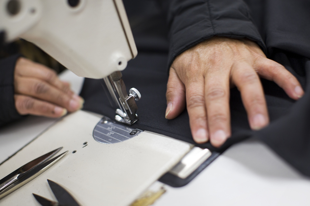 A worker sews a robe at a family-owned manufacturer in Chatsworth.