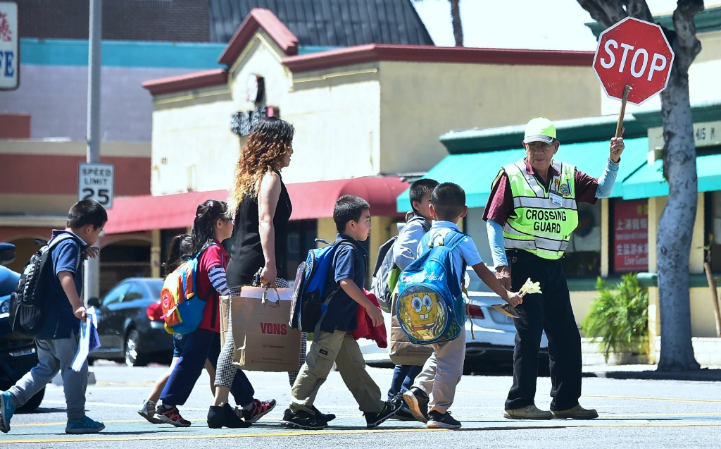 A school crossing guard stops traffic in Monterey Park, California on April 28, 2017. Many children in Southern California attend school in buildings within 500 feet of freeways, which is now prohibited by state law.