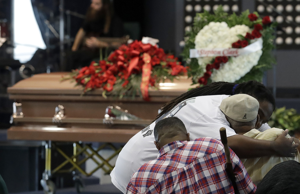 A man hugs another man before funeral services for Stephon Clark at Bayside Of South Sacramento Church, known as BOSS Church, in Sacramento, Calif., Thursday, March 29, 2018. Clark, who was unarmed, was shot and killed by Sacramento Police Officers on Sunday, March 18.  (AP Photo/Jeff Chiu, Pool)