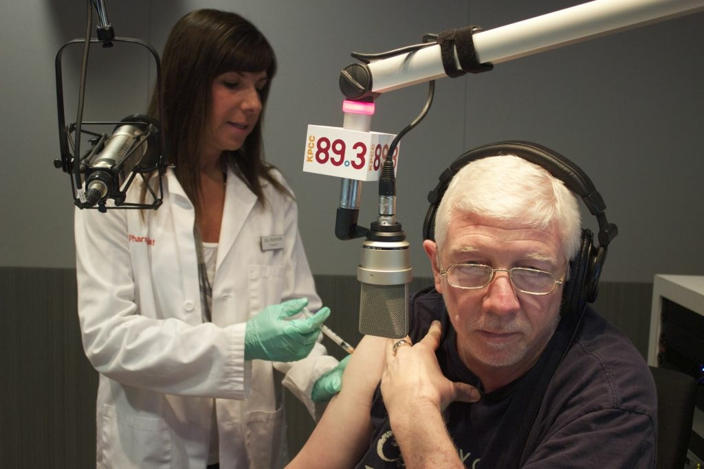 CVS Pharmacist Jill Kolin administers a flu shot to KPCC's Morning Edition Anchor Steve Julian.