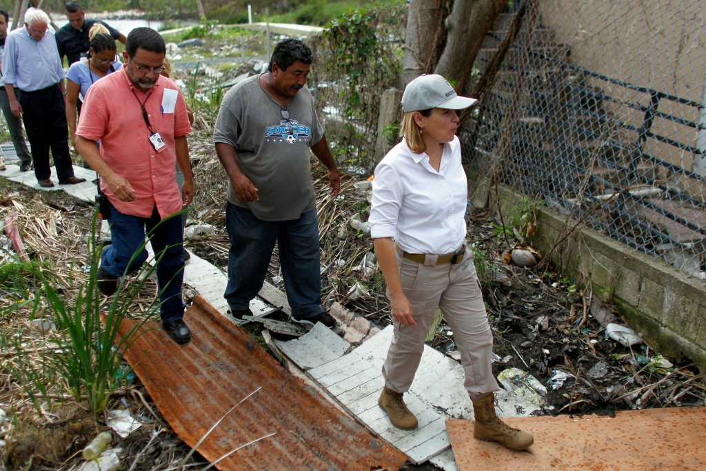 The mayor of San Juan, Carmen Yulin, walks over debris from Hurricane Maria during a visit with U.S. Sen. Bernie Sanders to the Playita community in San Juan, Puerto Rico, on October 27, 2017.
