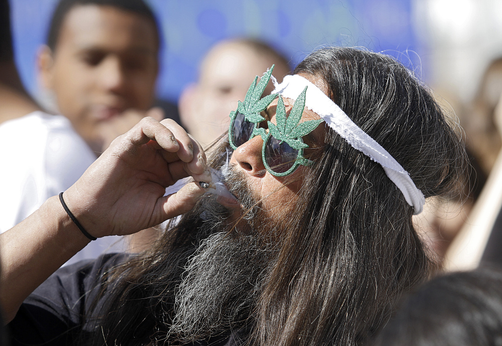 Fast Eddy Aki'a smokes a joint as thousands gathered to celebrate Colorado's medicinal marijuana laws.