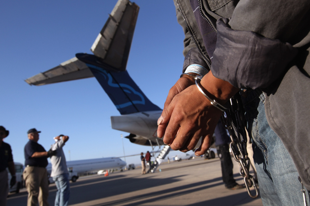 An undocumented Guatemalan immigrant, chained for being charged as a criminal, prepares to board a deportation flight to Guatemala City, Guatemala at Phoenix-Mesa Gateway Airport on June 24, 2011 in Mesa, Arizona.