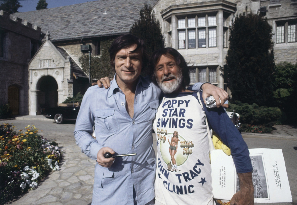 In this file photo, Hugh Hefner, left, poses at the Playboy Mansion at a fund-raising event for the John Tracy Clinic Tennis Tournament, May 20, 1978, Los Angeles, Calif. The man on the right is unidentified. Playboy Enterprise announced the West Los Angeles estate, the backdrop of many film shoots and wild parties, was listed on Monday, January 11, 2015, for $200 million.