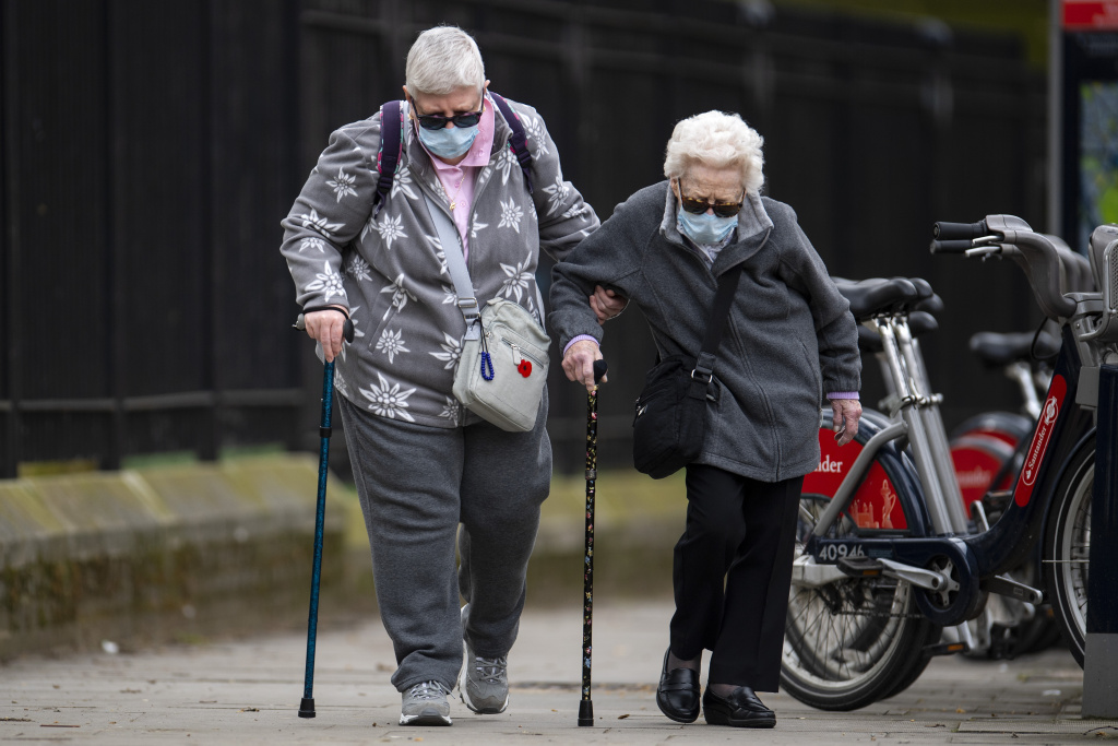 Elderly members of the public wearing face masks walk down a street.