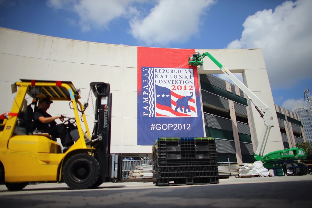 Workers hang a banner on the parking garage next to the Tampa Bay Times Forum where the Republican National Convention will be held on August 24, 2012 in Tampa, Florida.