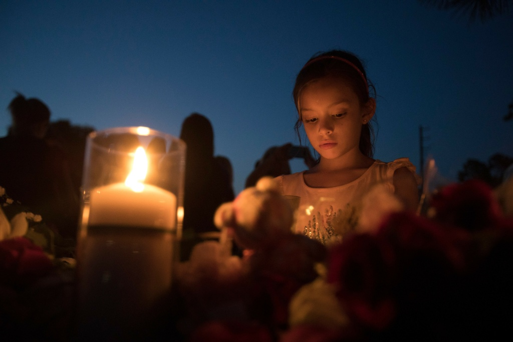 Lucretia Martinez, 7, stands before various momentos people have left during a candelight vigil in Santa Fe, Texas for the victims of the mass shooting on May 18, 2018.