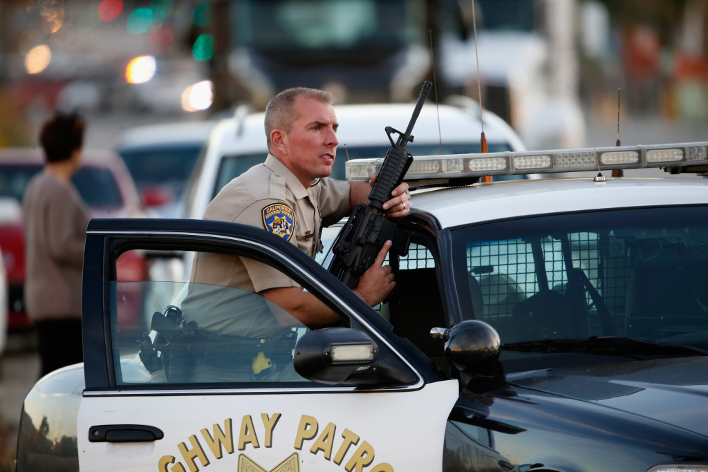 A California Highway Patrol officer stands with his weapon as authorities pursue the suspects in a shooting that occurred on December 2, 2015 in San Bernardino, California.