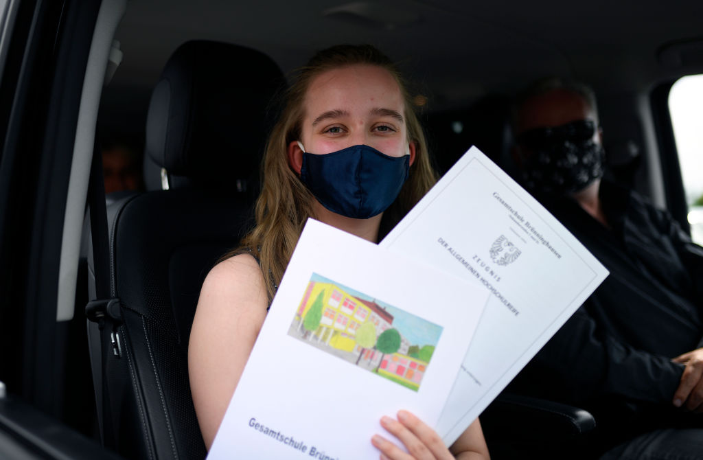 A high school graduate presents her baccalaureate certificate in her car during the ceremony of awarding of the Gesamtschule Bruenninghausen school at a drive-in cinema in Dortmund, western Germany, on June 18, 2020 during the coronavirus COVID-19 pandemic.