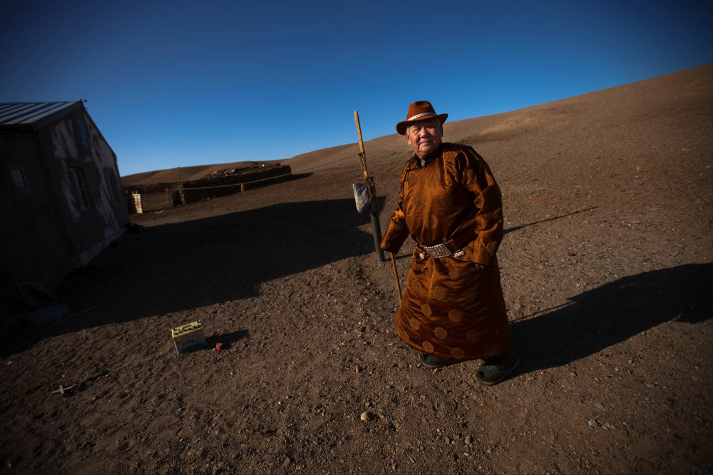 Herder Mijiddorj Ayur, 76, stands outside his home in South Gobi, Mongolia.