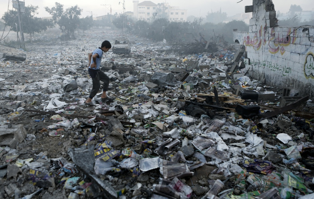 Caption:A Palestinian youth walks on debris as he inspects damages following an Israeli air strike in Gaza City, on July 24, 2014. Fifteen Palestinians were killed today when an Israeli shell slammed into a UN shelter where hundreds of civilians had taken refuge, sending the death toll in Gaza soaring to 788 despite world efforts to broker a ceasefire.