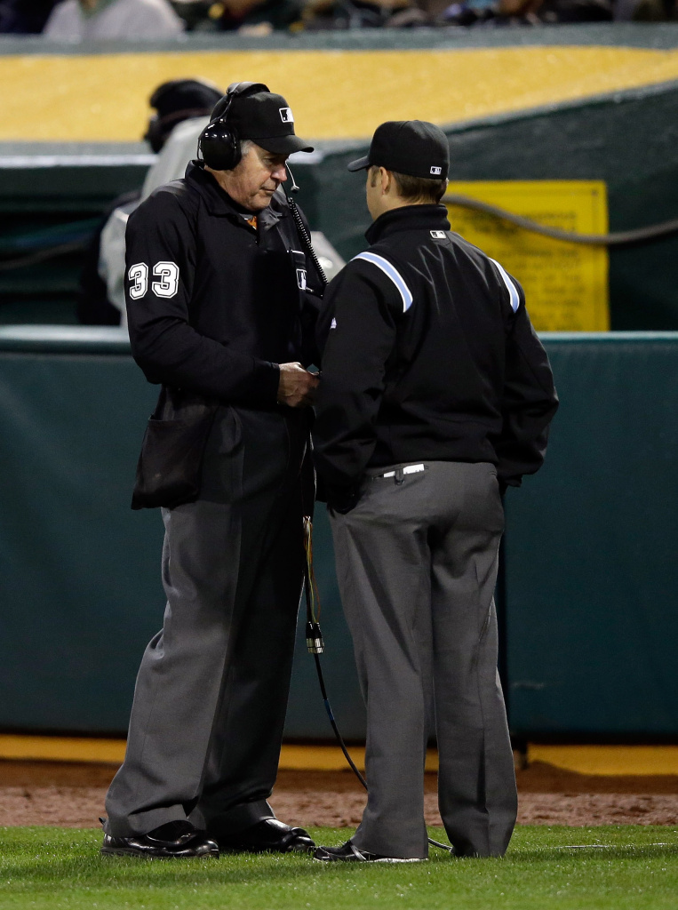 Umpires Mike Winters (L) and Mark Wegner review a play with instant replay in the sixth inning of their game between the Cleveland Indians and the Oakland Athletics during Opening Day at O.co Coliseum on March 31, 2014 in Oakland, California.  The ruling on the field stood.