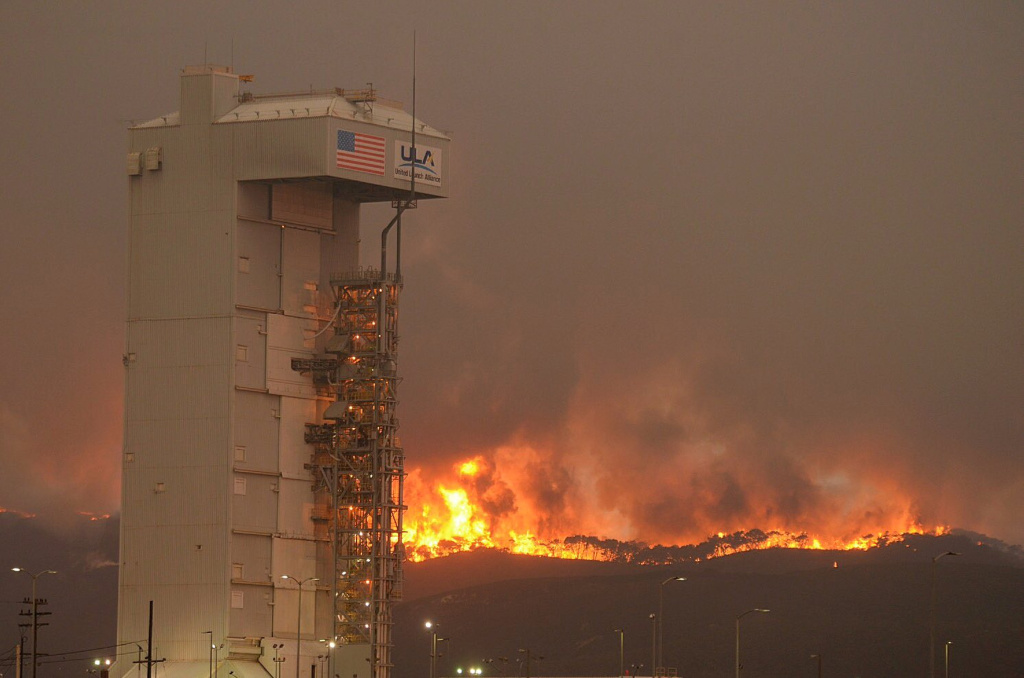 In this Monday, Sept. 19, 2016 photo provided by the Santa Barbara County Fire Department, a fire burns several miles behind Space Launch Complex-3, housing the Atlas V rocket & WorldView 4 satellite, at Vandenberg Air Force Base, Calif. Crews are working to surround the wildfire at the central California Air Force base that forced the postponement of a weekend satellite launch. The blaze has expanded to the south as it grew to more than 18 square miles.