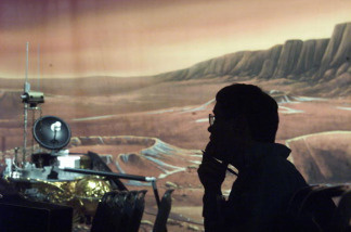 A reporter listens against a painted Martian backdrop at the Jet Propulsion Laboratory in Pasadena, California.