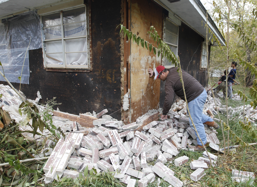 Chad Devereaux examines bricks that fell from three sides of his in-laws home in Sparks, Okla., following two earthquakes that hit the area in less than 24 hours. A study published Thursday, July 3, 2014 by the journal Science explains how just four wells forcing massive amounts of drilling wastewater into the ground are probably causing quakes in Oklahoma. The wells seem to have triggered more than 100 small-to-medium earthquakes in the past five years, according to a study.