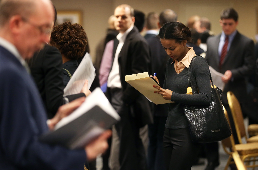 Applicants wait to meet potential employers at a Manhattan job fair on January 17, 2013 in New York City. Should recent graduates take the very first job offer they receive, or should they hold out for their dream position?