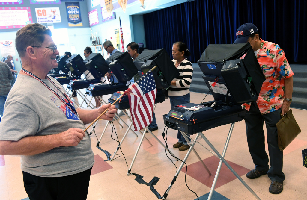Poll worker Jim Callahan (L) uses an American flag to direct voters to available voting machines at a polling station at John W. Bonner Elementary School on Election Day on November 8, 2016 in Las Vegas, Nevada.