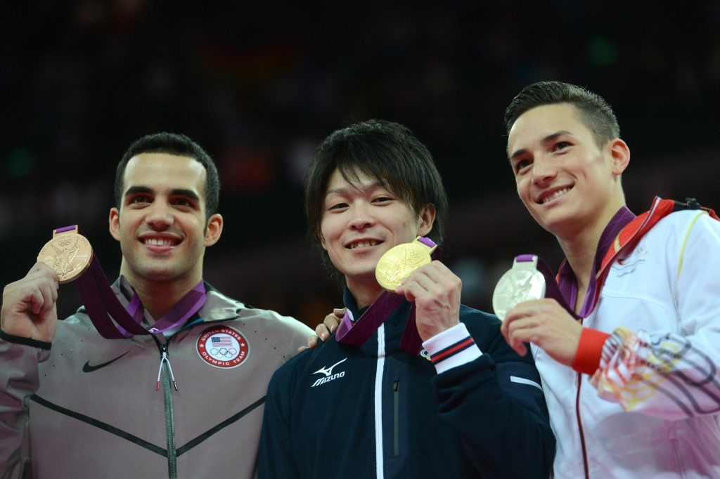 Gold medalist Japan's gymnast Kohei Uchimura (center), silver medalist Germany's Marcel Nguyen (right) and bronze medalist Danell Leyva (left) celebrate on the podium of the men's individual all-around competition.