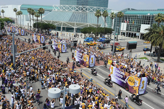 Fans cheers as The Los Angeles Lakers ride down the street on double decker buses during their 2009 NBA championship victory parade, in downtown Los Angeles, California on June 17, 2009. The Lakers say they are going to pay for the parade if they win this year.