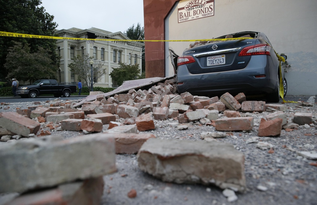 Bricks and fallen rubble cover a car with the old courthouse in the background following an earthquake Sunday, Aug. 24, 2014, in Napa, Calif. A large earthquake rolled through California's northern Bay Area early Sunday, damaging some buildings, igniting fires, knocking out power to tens of thousands and sending residents running out of their homes in the darkness.