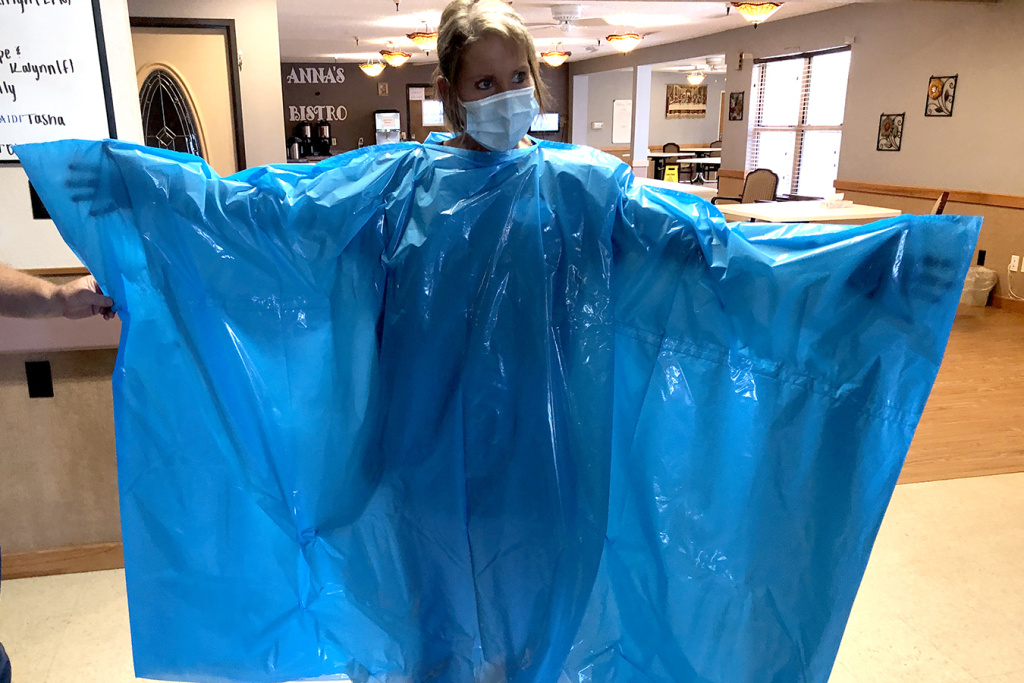 Kelly Womochil, an aide at Enterprise Estates Nursing Center in Enterprise, Kan., tries on a poncho that the Federal Emergency Management Agency is sending to nursing homes to protect against the coronavirus.