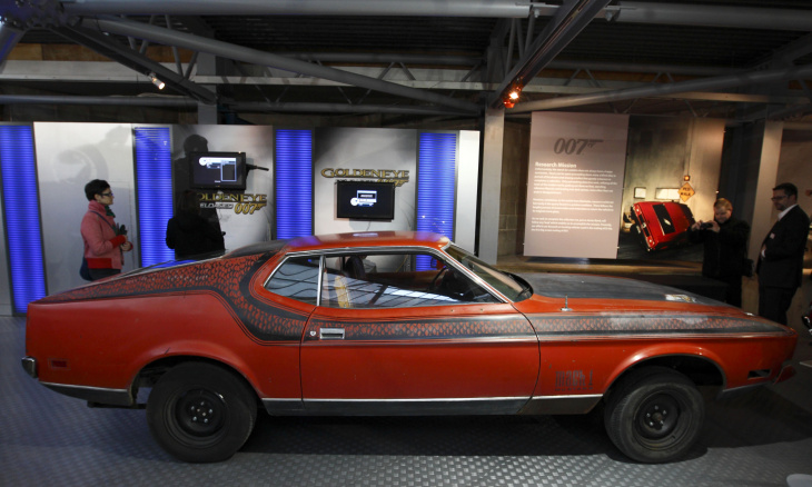 Visitors look at the Ford Mustang Mach 1