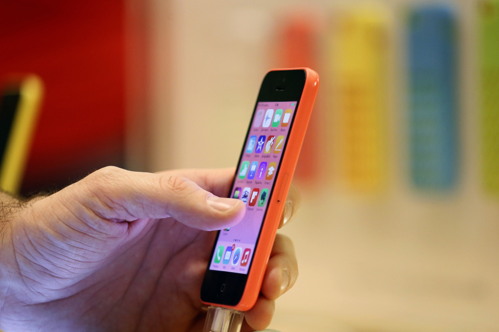 A woman looks at an Apple iPhone at one of the company's stores in Paris, on December 20, 2013.