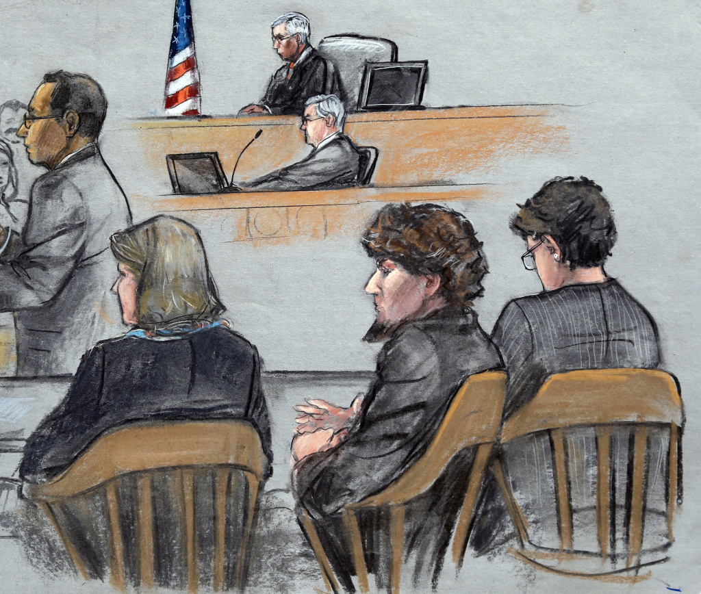 In this April 2015 courtroom sketch, Assistant U.S. Attorney Aloke Chakravarty, left, is depicted addressing the jury as defendant Dzhokhar Tsarnaev, second from right, sits between his defense attorneys. Jurors now must weigh any mitigating factors they find against any aggravating factors to determine Tsarnaev's sentence.