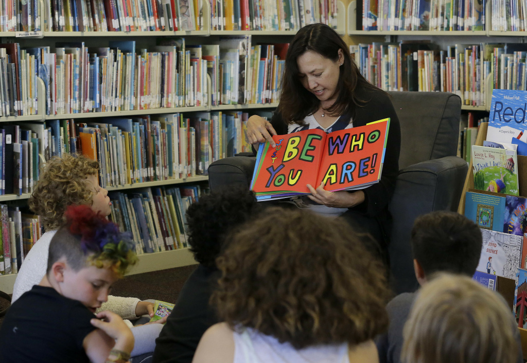 "In this Wednesday, July 12, 2017 photo, Sandra Collins, executive director and founder of enGender, reads a book to campers at the Bay Area Rainbow Day Camp in El Cerrito, Calif. Collins says, ""A lot of these kids have been bullied and had trauma at school. This is a world where none of that exists, and they're in the majority. That's a new experience for kids who are used to hiding and feeling small."" (AP Photo/Jeff Chiu)"