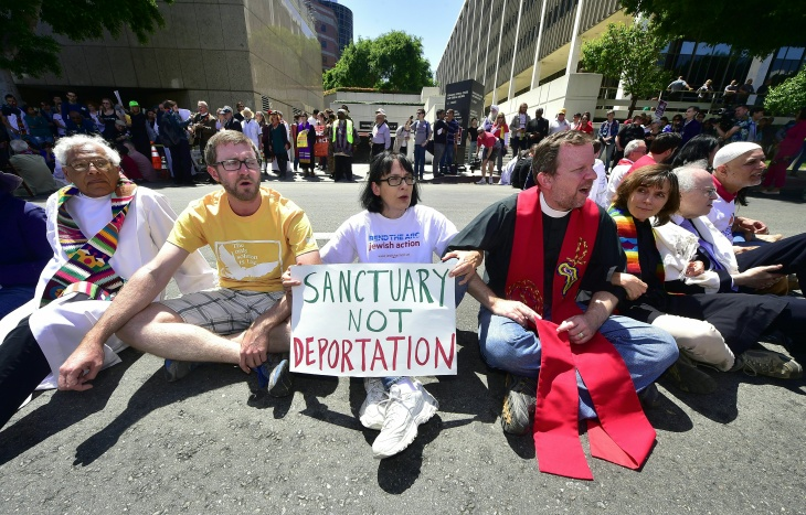 Police arrest demonstrators protesting recent enforcement actions by federal Immigration and Customs Enforcement (ICE) personnel outside the ICE headquarters on downtown Los Angeles, California on April 13, 2017. Some three dozen people were arrested in the